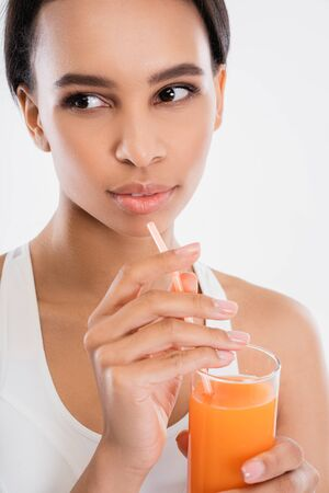 Thoughtful lady drinking fresh juice in glass