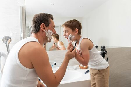 Happy father and son are standing near miror and shaving