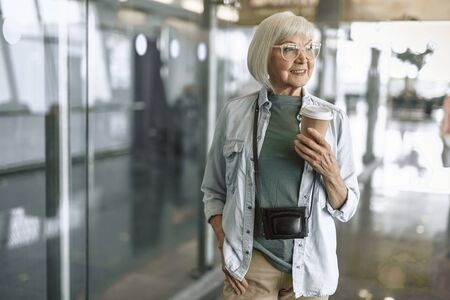 Happy mature lady having rest with coffee in hall before check in