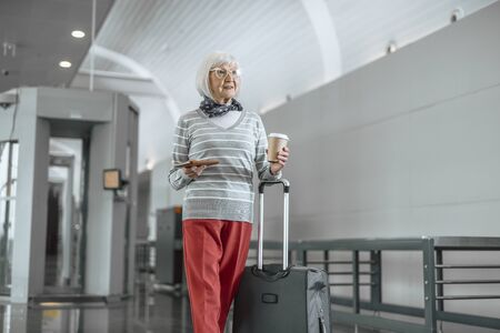 Cheerful mature lady with luggage enjoying travel 写真素材 - 124908138