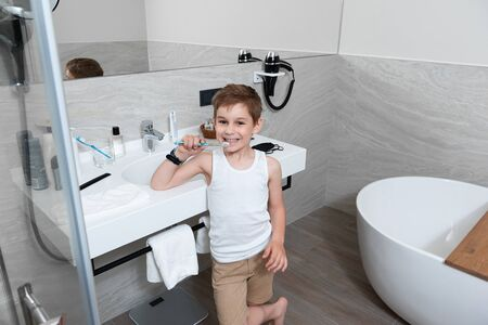 Little boy is holding a toothbrush in bathroom