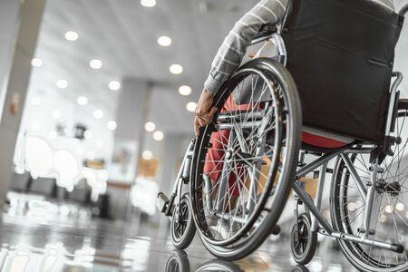 Oudere dame gebruikt een rolstoel op de luchthaven