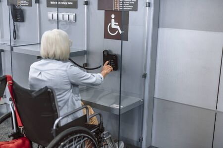 Mature woman on disabled carriage calling at airport