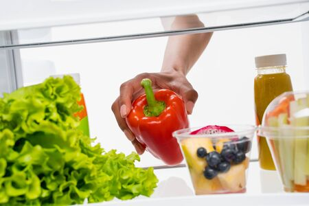 Ladys hand taking sweet pepper from refrigerator