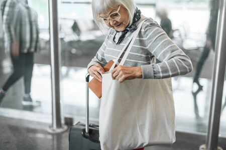 Cheerful senior woman staying at hall with baggage Banco de Imagens