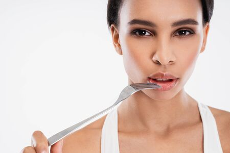 Young slender lady holding fork close to lips