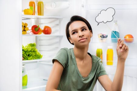 Young smiling lady thinking what food to choose Фото со стока