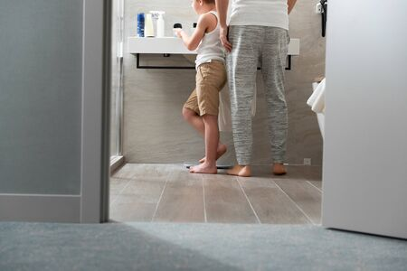 Adult father and son are standing in the bathroom Reklamní fotografie