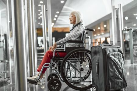 Smiling mature lady on disabled carriage looking forward at airport