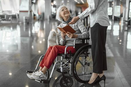 Female worker of airport talking to elderly woman in wheelchair at hall