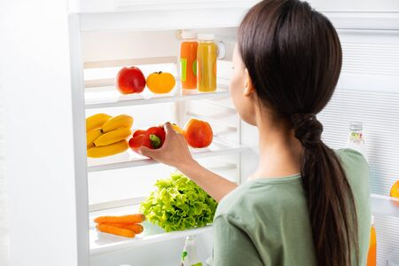 Young lady taking sweet pepper from refrigerator Фото со стока