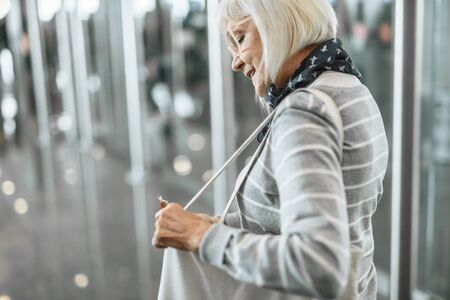 Confident mature lady is standing at airport