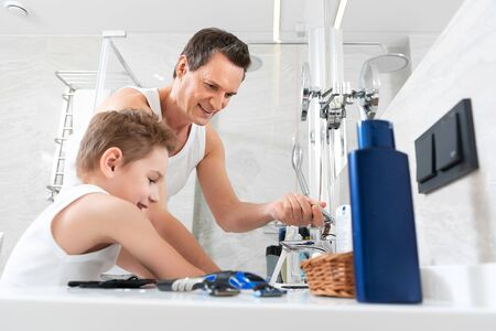 Father and son doing morning procedure together in bathroom