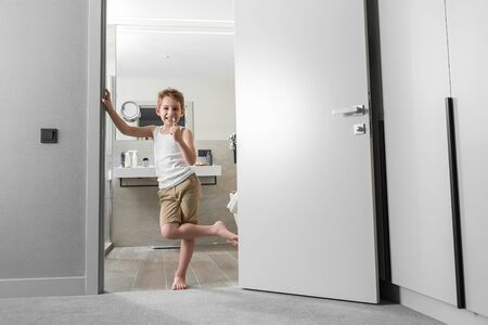 Smiling boy is holding a toothbrush near door