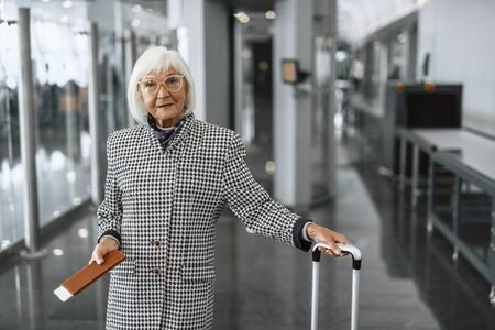 Cheerful senior lady staying at hall and ready for check in