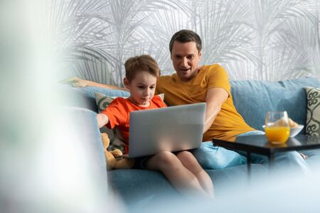 Father and son sitting on sofa in room Imagens
