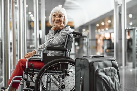 Happy mature lady on disabled carriage waiting for trip at hall