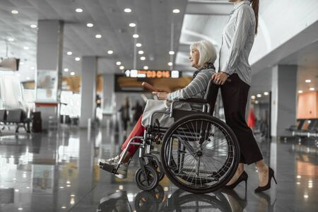 Female worker standing near elderly woman in wheelchair at airport