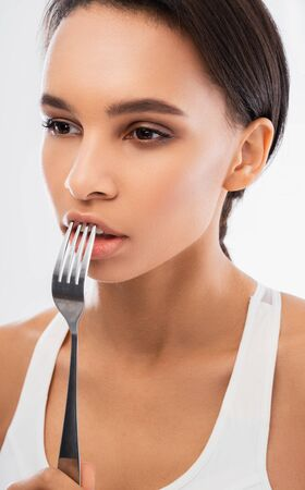 Young lady touching her lips by fork