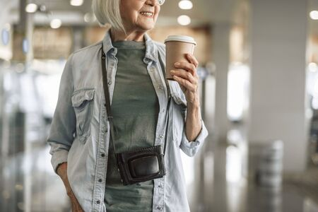 Happy old woman staying in hall with coffee Banco de Imagens