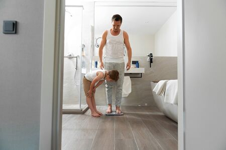 Dad and son measuring weight in the bathroom at home Banco de Imagens