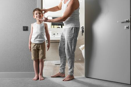 Happy father and little son measuring height at bathroom