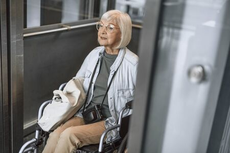 Smiling old female on disabled carriage using lift