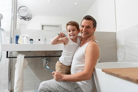 Father and son doing morning procedure in bathroom Stockfoto