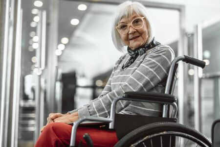Mature lady on wheelchair waiting for trip at hall 版權商用圖片