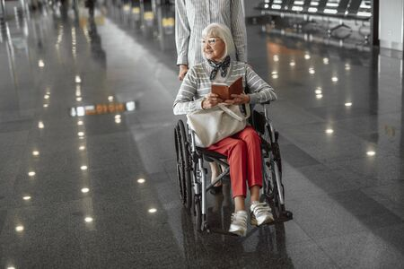 Young female worker moving elderly woman in wheelchair at airport