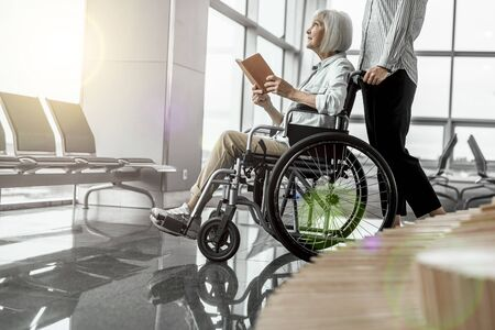Young female worker standing near elderly woman in wheelchair at airport Reklamní fotografie
