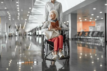 Young female worker of airport holding wheelchair with elderly lady in hall 版權商用圖片