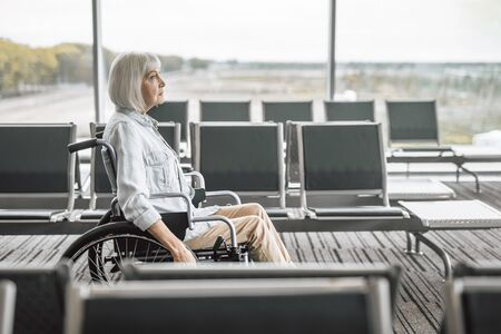 Cheerful mature woman on disabled carriage near panoramic windows