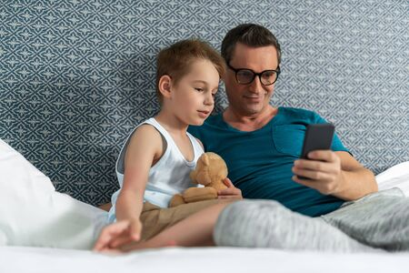 Father in glasses and son lying in bed in room