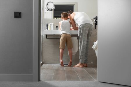 Dad and son doing morning procedure in bathroom