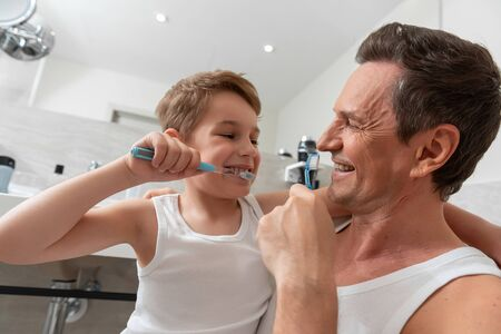 Father and son holding toothbrushes in bathroom Banco de Imagens