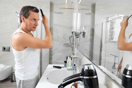 Adult man is combing in the bathroom
