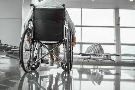 Elderly woman is using a wheelchair in airport