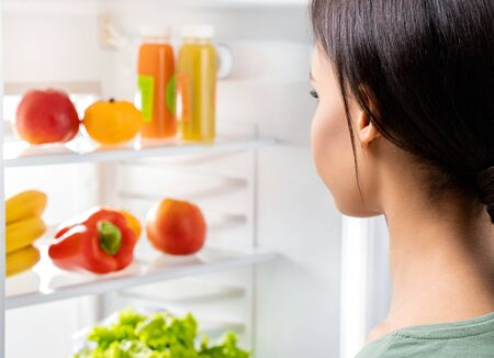 Young lady looking at fresh food in refrigerator