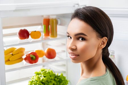Lady staying before refrigerator with organic food