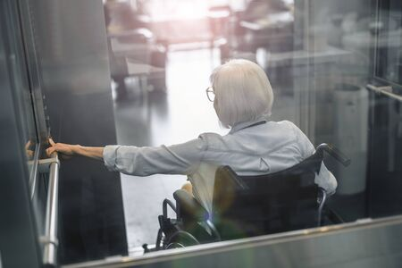 Mature woman on disabled carriage using lift Stock Photo