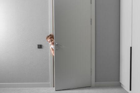 Niño está mirando por la puerta