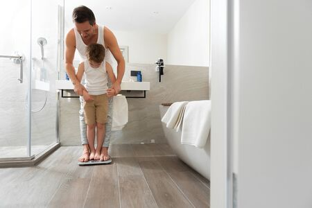 Dad and son measuring weight together at home