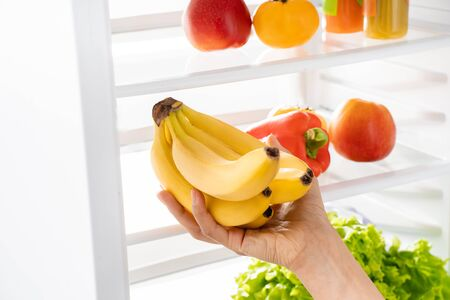 Young lady hand taking bananas from refrigerator