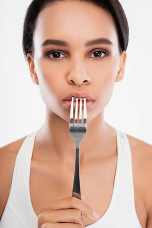 Young lady holding fork close to lips
