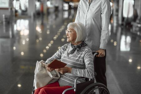 Female worker of airport helping elderly woman in wheelchair at hall