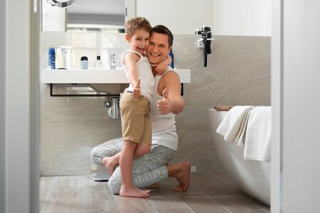 Smiling father and son staying in bathroom at home Banco de Imagens