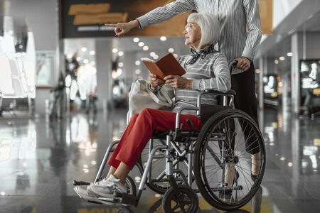 Female worker of airport staying with elderly woman in wheelchair at hall
