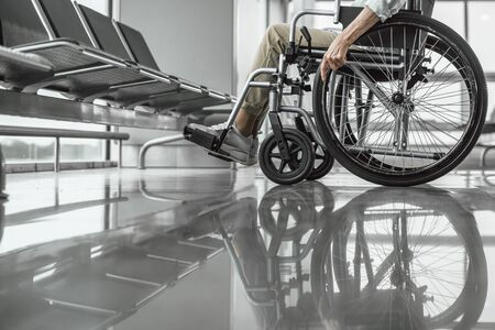 Mature lady on disabled carriage at airport Stock Photo