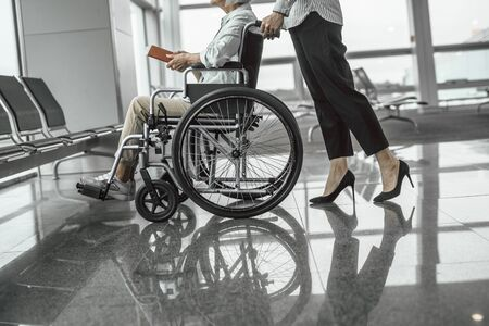 Young female worker moving elderly woman in wheelchair at hall